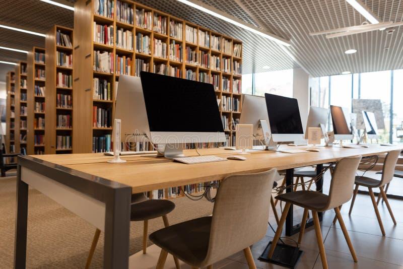 空的电脑室在学校图书馆中 现代计算机在一张木桌上站立 库存照片
