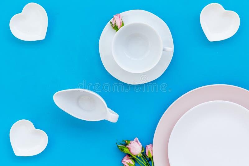 空的白色和桃红色五颜六色的板材和为设置在蓝色桌backgroung顶视图的桌上升了 图库摄影