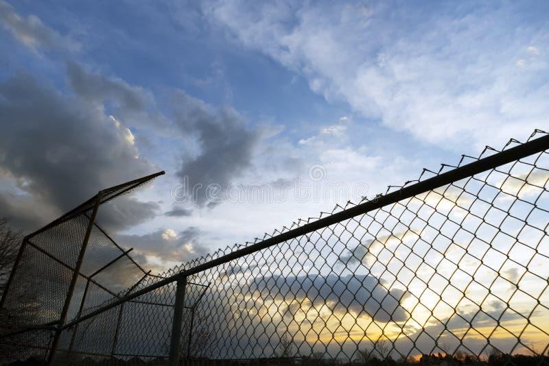 空的社区内野和篱芭在剪影反对 库存图片