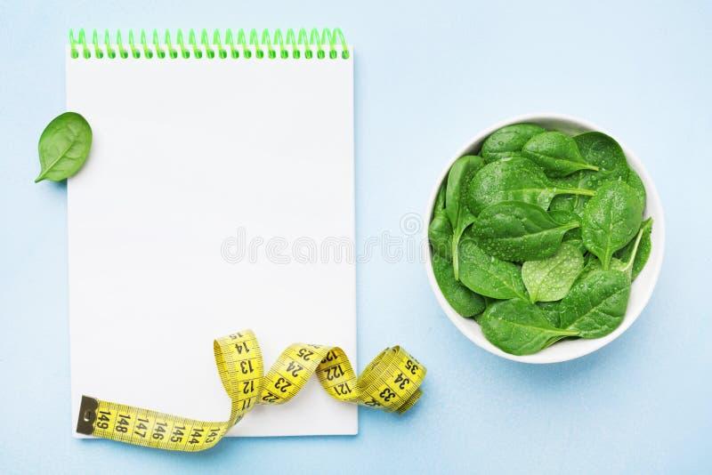 空的笔记本、绿色菠菜叶子和卷尺在蓝色台式视图 饮食和健康食物概念 免版税库存图片