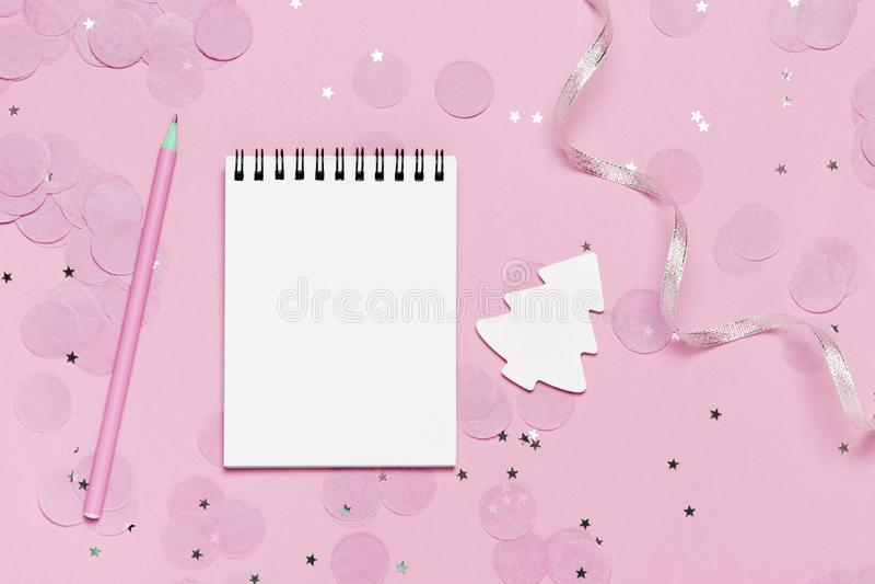 空的笔记本-模板的圣诞节和新年嘲笑与在桃红色背景的桃红色五彩纸屑 免版税图库摄影