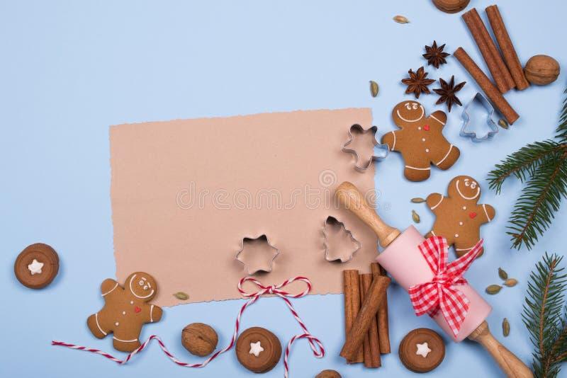 空的纸片写的食谱和成份烘烤的,厨房用具,香料,姜饼人曲奇饼 顶视图 免版税库存图片