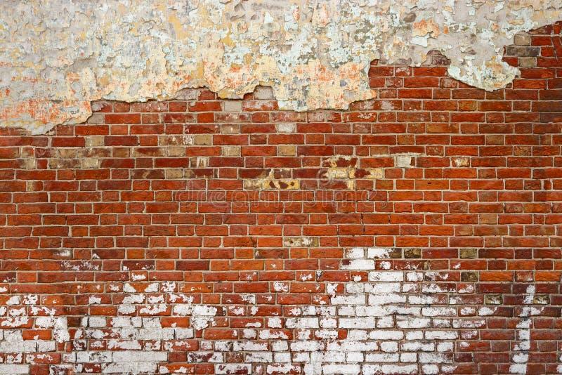 空的老砖墙纹理 被绘的困厄的墙壁表面 难看的东西红色阻碍背景 破旧的大厦门面以损伤 免版税库存照片