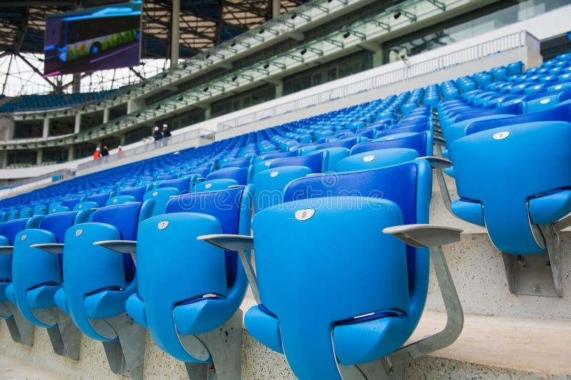 空的蓝色位子在体育场内 免版税库存照片