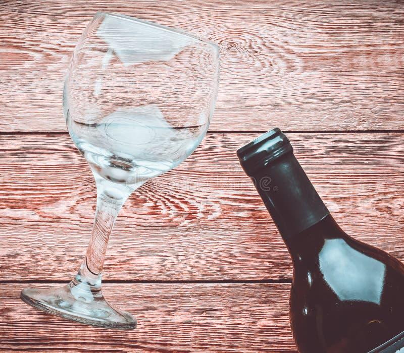 空的酒杯和一个瓶在一张木桌上的酒 免版税库存图片