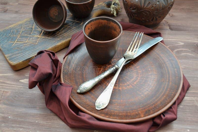 空的陶瓷餐具和木objets有石榴汁糖浆餐巾平的视图 库存图片