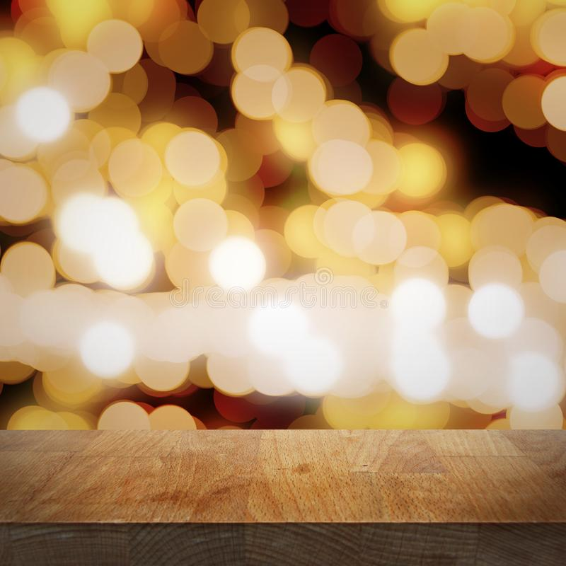 空的顶面木桌、被弄脏的金黄夜背景与光和bokeh,焦点在桌面 免版税库存照片