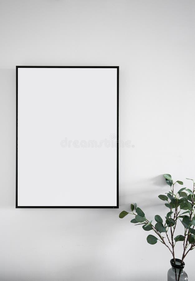 空的黑木制框架的构成安装在有人为植物的白色被绘的墙壁角落/室内设计的/isol 免版税图库摄影