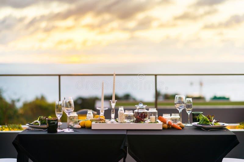 空的玻璃在餐馆-饭桌设置了户外在日落 免版税库存照片