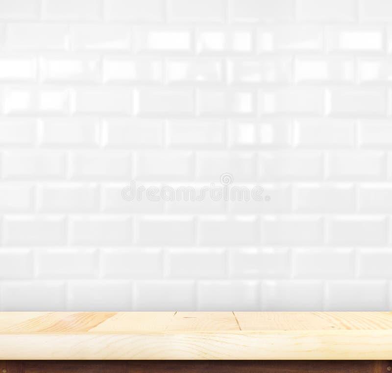 空的轻的木桌和白色陶瓷砖砖墙后面 免版税图库摄影