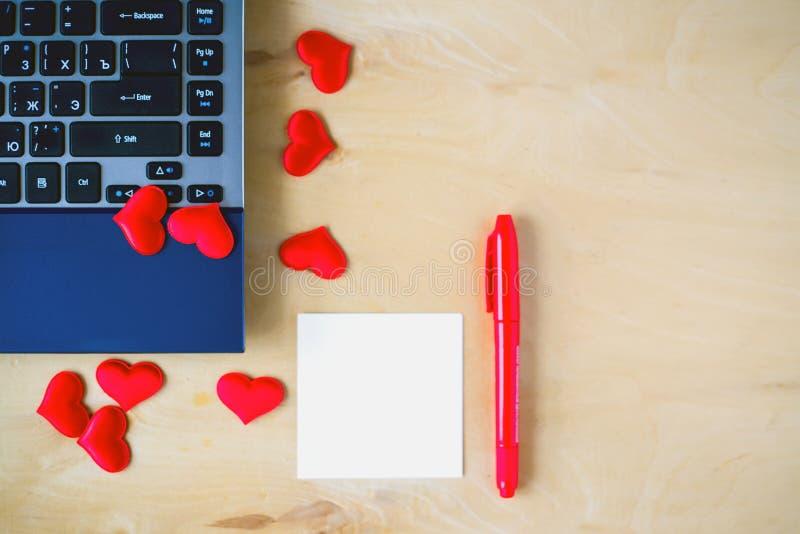 空的贴纸、个人计算机、笔和心脏在木桌上 库存图片