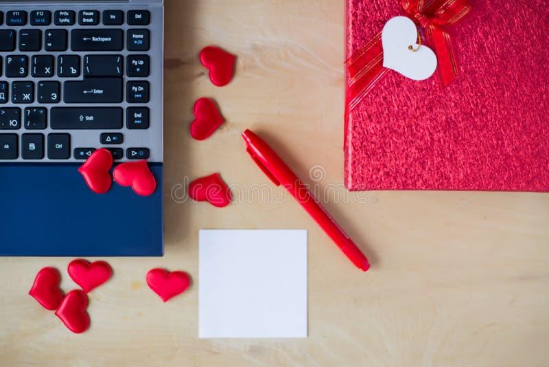 空的贴纸,个人计算机,笔,箱子装饰了在木桌上的心脏 免版税库存图片