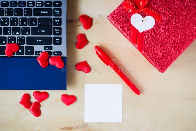 空的贴纸,个人计算机,笔,箱子装饰了在木桌上的心脏 库存图片