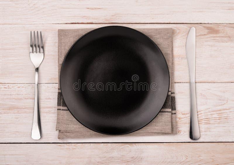 空的黑色的盘子、银器和餐巾顶视图  库存照片