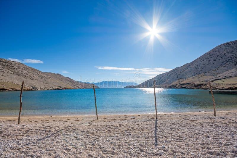 空的Pebble海滩用木棍子和海湾的闪烁的海 免版税库存图片