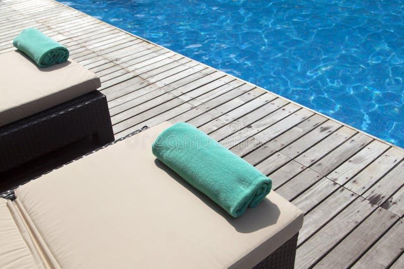 空的sunbeds临近游泳池 免版税库存照片
