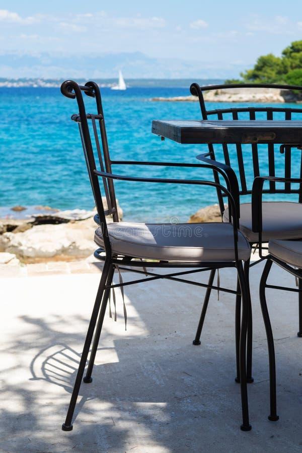 空置椅子和桌在酒吧在海滩旁边在克罗地亚海岛乌格连岛上 库存照片