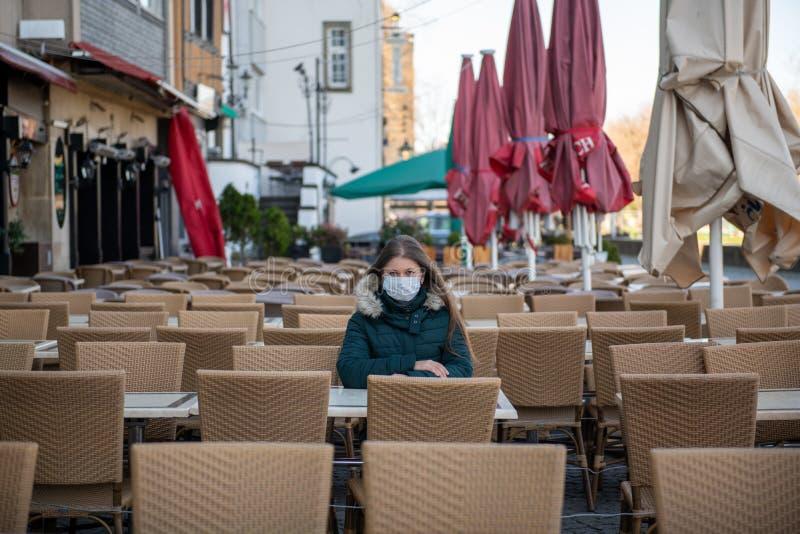 空荡荡的咖啡馆露台上戴医用口罩的妇女 图库摄影