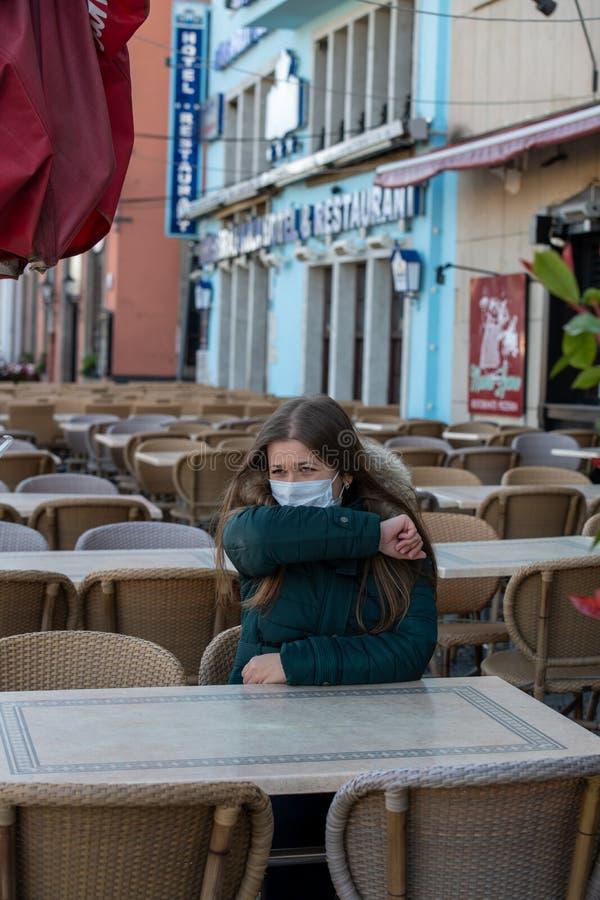 空荡荡的咖啡馆露台上戴医用口罩的妇女 免版税库存照片