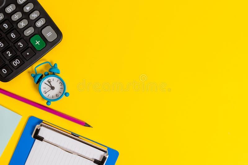 空金属减速火箭的葡萄酒闹钟醒来空白纸剪贴板笔记薄计算器铅笔说谎的色的背景 免版税库存照片