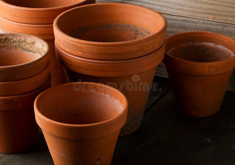 空,半新赤土陶器种植在木桌上的小组罐 图库摄影