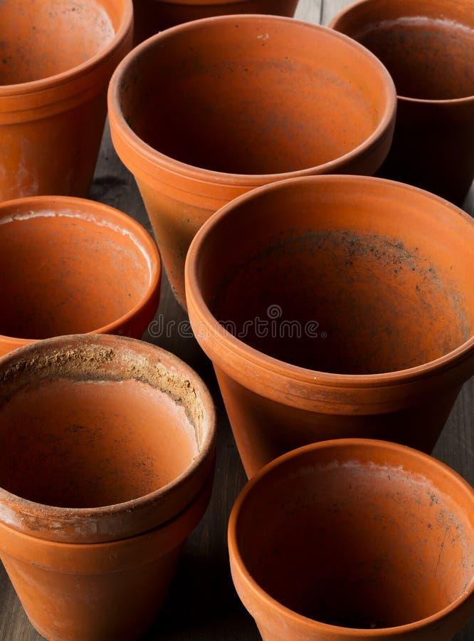 空,半新赤土陶器种植在木桌上的小组罐 免版税库存图片