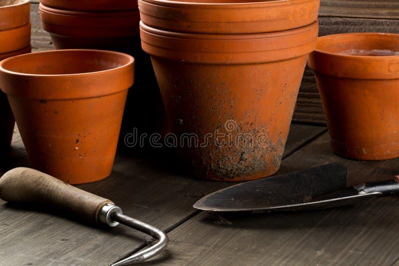 空,半新赤土陶器种植在木桌上的小组罐 库存照片