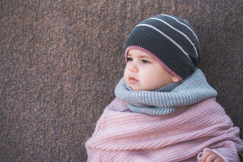 穿一个温暖的冬天帽子和一条五颜六色的围巾在棕色背景的逗人喜爱的女婴 免版税库存图片