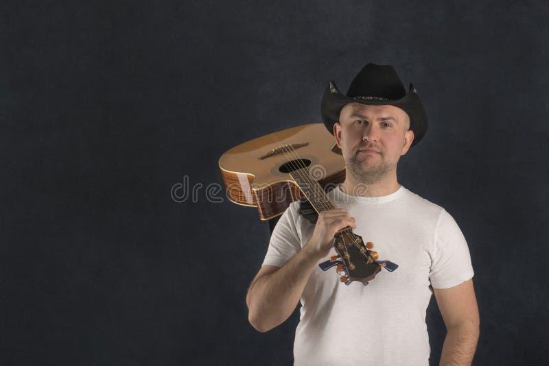 穿一个黑牛仔帽和白色T恤的年轻人的画象运载在他的肩膀的一把吉他反对黑暗 库存照片