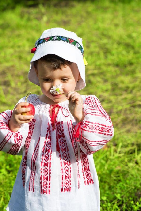 穿一件传统罗马尼亚女衬衫的小女孩命名了ie和嗅到花 图库摄影