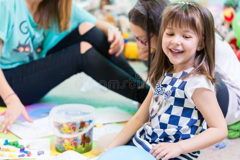 穿一件时髦T恤杉的快乐的幼儿园女孩,当使用时 免版税库存照片