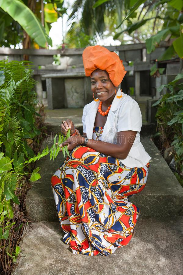 穿一件明亮的五颜六色的全国礼服的一名快乐的非裔美国人的妇女的垂直的充分的身体在庭院里坐 库存图片