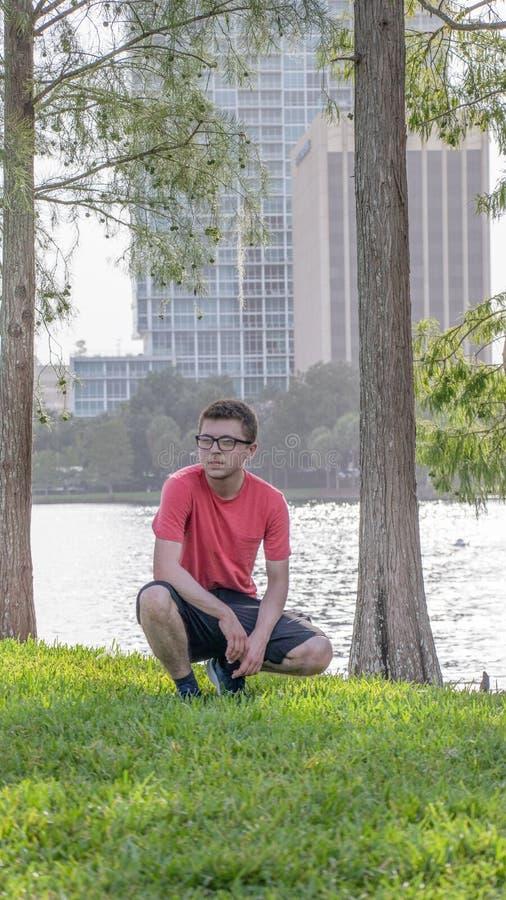 穿一件明亮的红色T恤杉的年轻人 免版税图库摄影