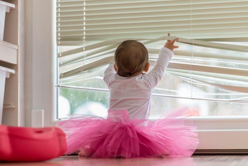 穿一件桃红色芭蕾舞短裙的逗人喜爱的矮小的女婴 库存图片