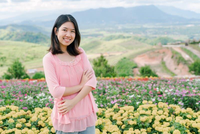 穿一件桃红色衬衣的亚裔美女站立愉快地微笑在后边一个黄色花园里是山景 免版税库存图片