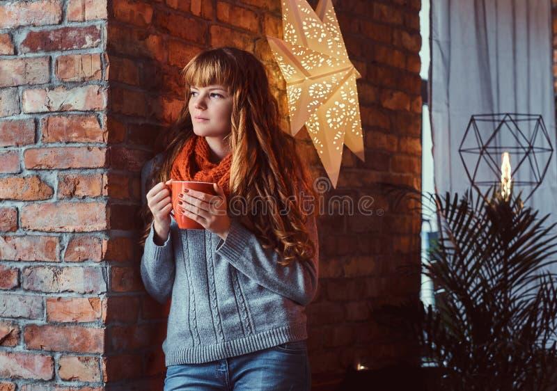 穿一件温暖的毛线衣的一个孤独的红头发人女孩的画象拿着一杯咖啡,当倾斜在砖墙时 免版税库存图片