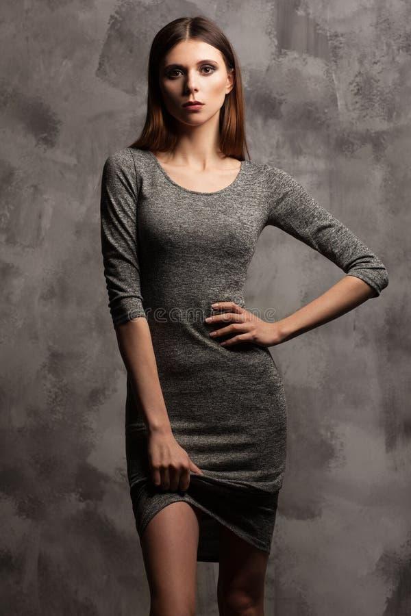 穿一件灰色礼服的一名美丽的亭亭玉立的妇女的照片 灰色察觉了背景 库存图片