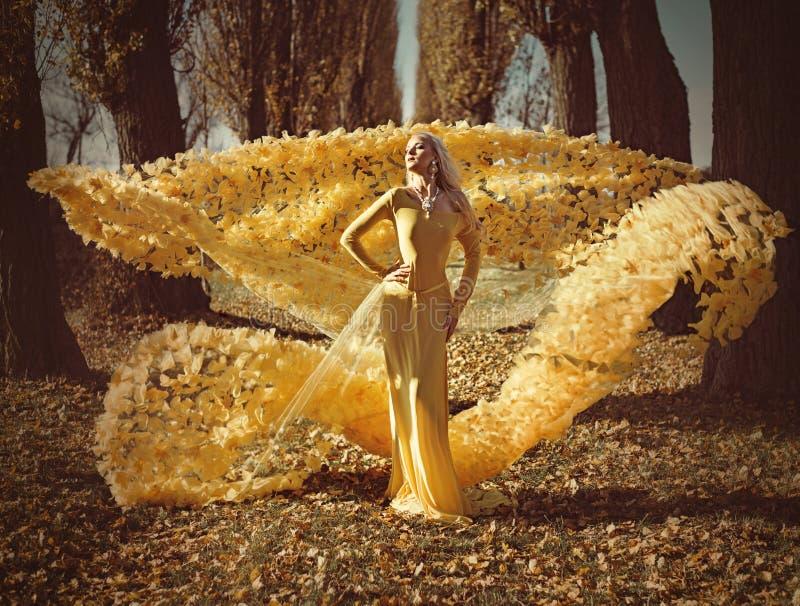 穿一件用花装饰,金黄褂子的金发碧眼的女人的画象 免版税图库摄影
