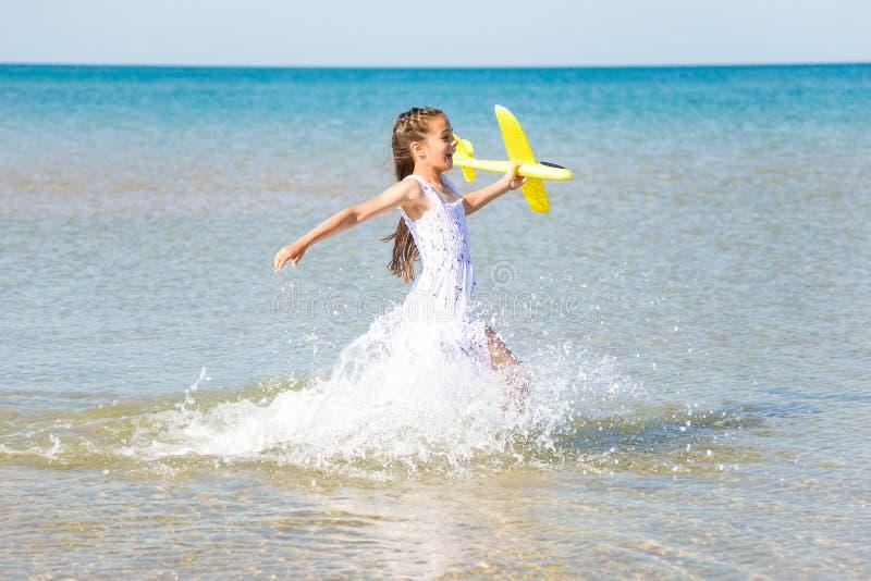 穿一件白色礼服的逗人喜爱的愉快的女孩运行通过海水和使用与黄色玩具pl 免版税图库摄影