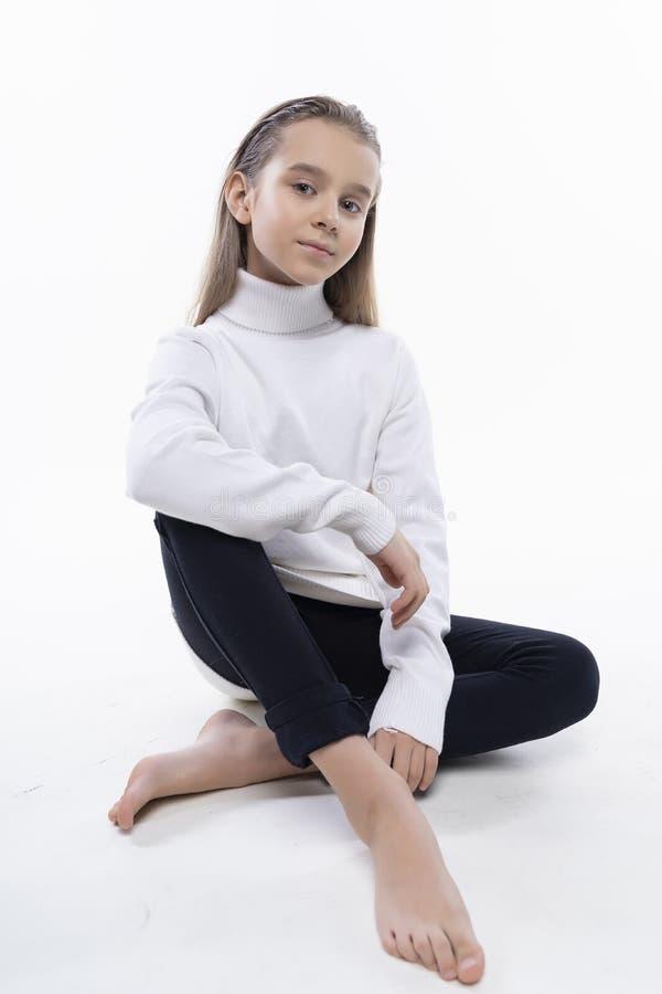 穿一件白色高领衫毛线衣和牛仔裤的美丽的逗人喜爱的青少年的女孩坐地板 r ?? 免版税库存图片