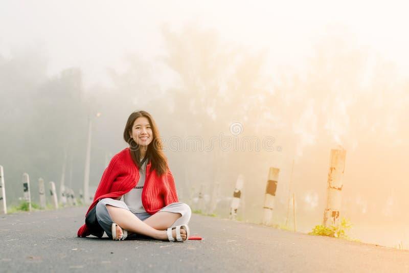 穿一件红色毛线衣的亚裔少年坐在路中间由在早晨薄雾和早晨阳光的水库 免版税库存照片