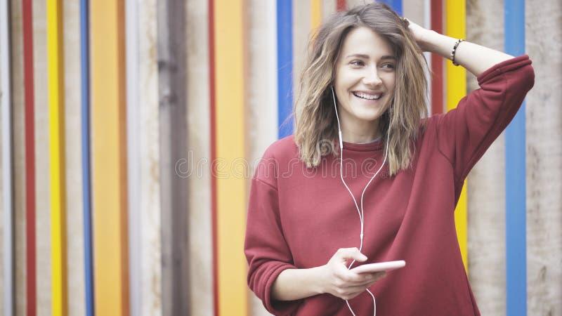 穿一件红色毛线衣的年轻公平的头发妇女站立在听到与她的耳机的音乐的五颜六色的墙壁附近和 免版税库存照片