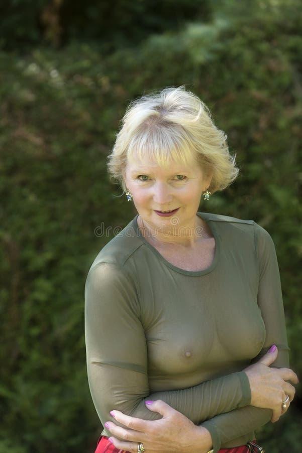 穿一件纯粹衬衣的白肤金发的妇女 库存照片