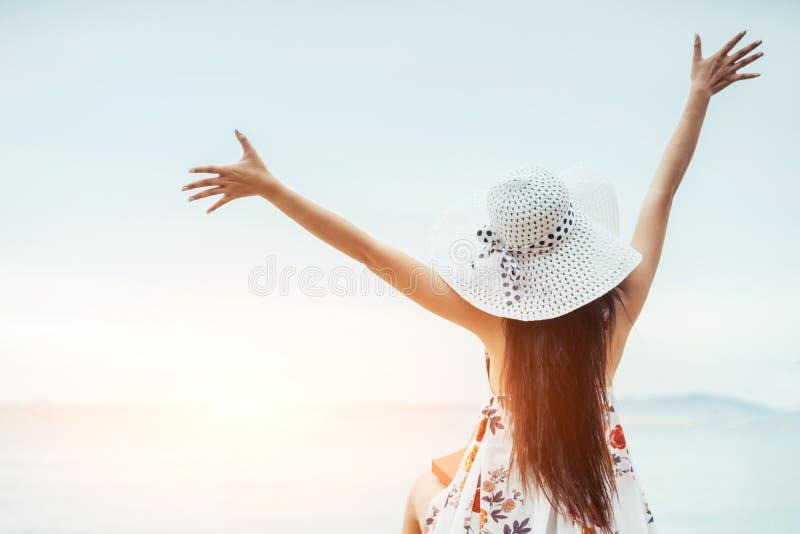 穿一件长的白色礼服的亚裔女孩走或坐在海滩 免版税库存照片