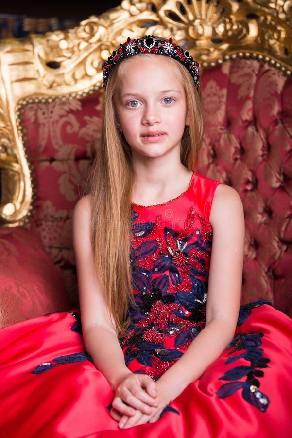 穿一套古色古香的公主礼服或服装的逗人喜爱的矮小的红头发人女孩 图库摄影