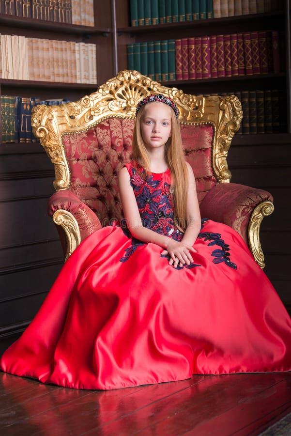 穿一套古色古香的公主礼服或服装的逗人喜爱的矮小的红头发人女孩 免版税库存图片