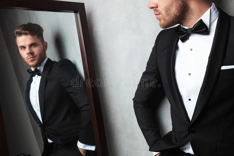 穿一套黑无尾礼服的轻松的年轻人的镜象反射 免版税库存照片