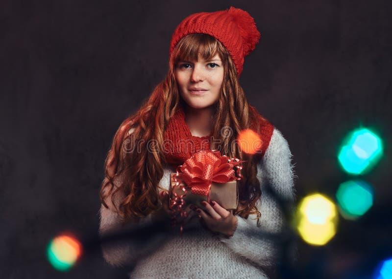 穿一条温暖的毛线衣和围巾的一个美丽的微笑的红头发人女孩的画象拿着礼物盒 库存图片