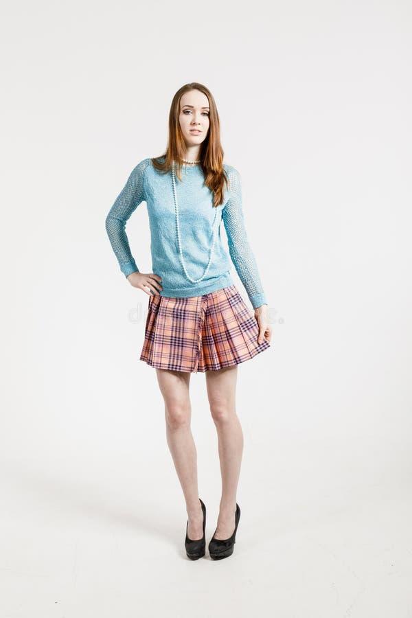 穿一条短裙和绿松石套头衫的年轻女人的图象 免版税库存照片