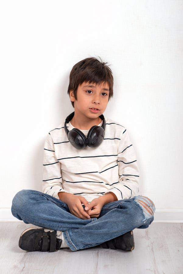 穿一白色衬衫和牛仔裤有耳机的一个年轻男孩选址在地板上由墙壁和考虑或哀伤某事 免版税图库摄影